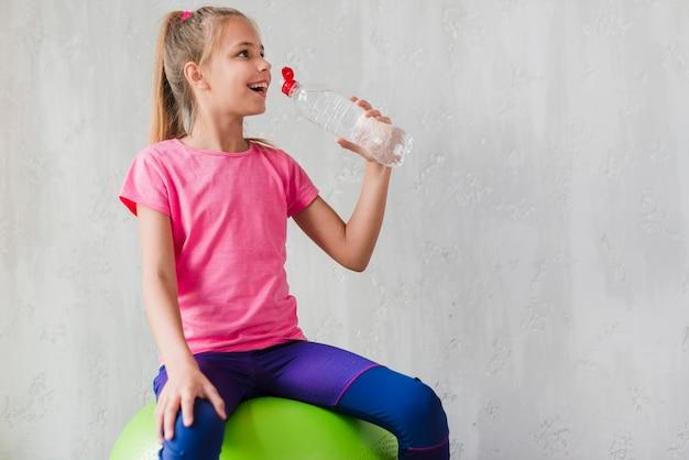 Muchacha sonriente que se sienta en la bola verde de los pilates que bebe el agua de la botella contra el muro de cemento Foto gratis