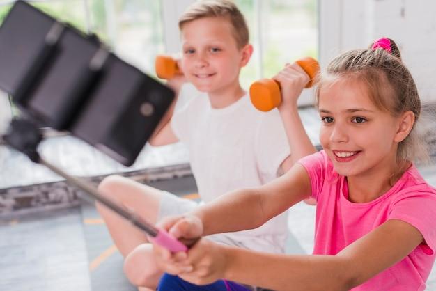 Muchacha sonriente que toma el selfie en el teléfono móvil que se sienta con su amigo que ejercita con pesas de gimnasia Foto gratis