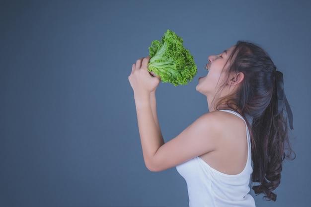 La muchacha sostiene las verduras en un fondo gris. Foto gratis