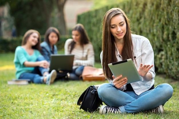 La muchacha de universidad sonriente está sosteniendo la pc de la tableta. Foto Premium
