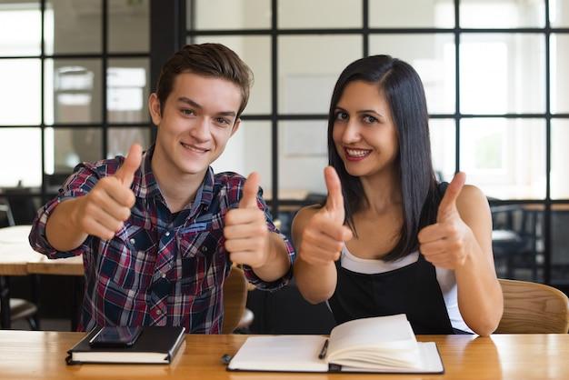 Muchacho acertado y muchacha del estudiante joven que muestran los pulgares para arriba Foto gratis
