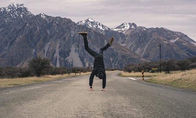Un muchacho asiático que hace la parte posterior del tirón al aire libre en el camino con la montaña de la nieve Foto Premium