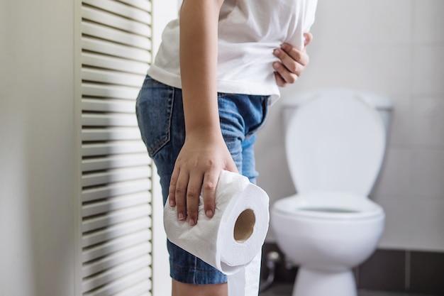 Muchacho asiático que se sienta en la taza del inodoro que sostiene el papel de tejido - concepto del problema de salud Foto gratis