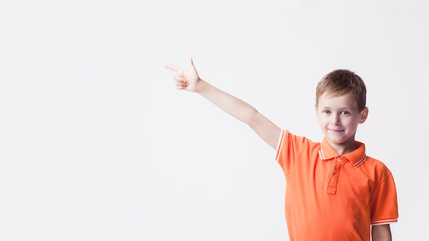 Muchacho caucásico sonriente que señala el dedo índice al lado en el contexto blanco Foto gratis