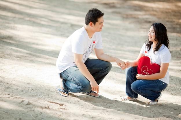 Muchacho joven que lleva a cabo su mano bonita de la novia en la playa Foto Premium