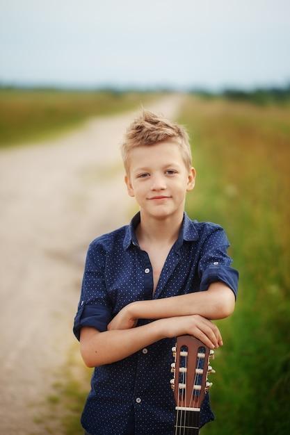 El muchacho lindo hermoso está sosteniendo la guitarra acústica en al aire libre Foto Premium