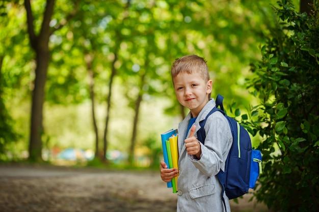 El muchacho lindo del niño con los libros y la mochila, muestra la clase en fondo verde de la naturaleza. volver al concepto de escuela. Foto Premium