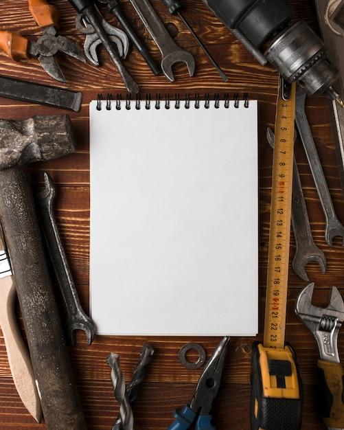 Muchas herramientas prácticas y cuaderno en blanco sobre mesa de madera, vista superior Foto Premium