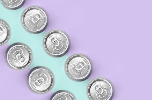 Muchas latas de cerveza metálicas sobre fondo de textura de pastel de moda Foto Premium