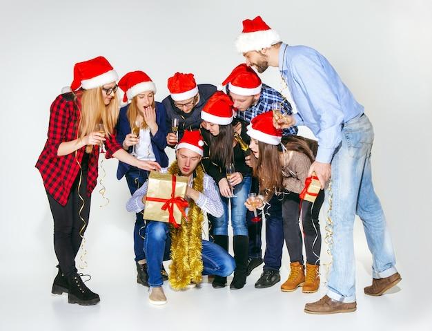 Muchas mujeres y hombres jóvenes bebiendo en la fiesta de navidad en estudio blanco Foto gratis