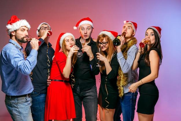 Muchas mujeres y hombres jóvenes bebiendo en la fiesta de navidad en estudio rosa Foto gratis