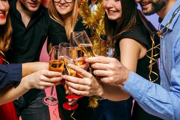 Muchas mujeres y hombres jóvenes bebiendo en la fiesta de navidad Foto gratis