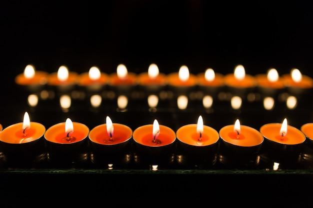 Muchas velas encendidas con poca profundidad de campo. Foto Premium