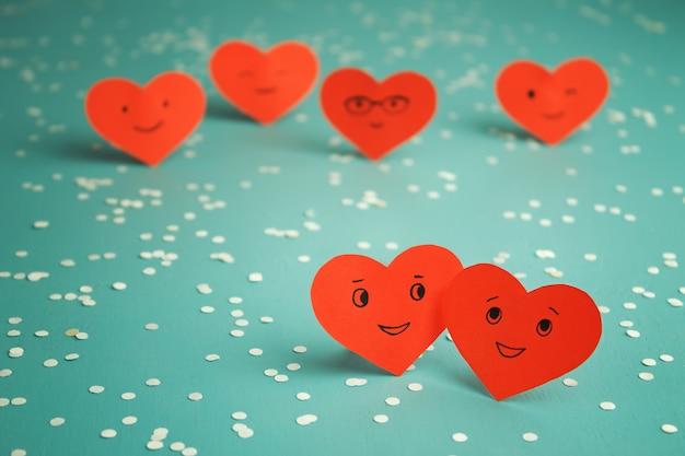 Muchos corazones sonrientes rojos en una tabla azul. día de san valentín. pareja enamorada. Foto Premium