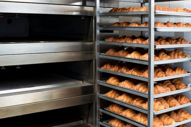 Muchos croissant recién horneado en un horno de panadería Foto gratis