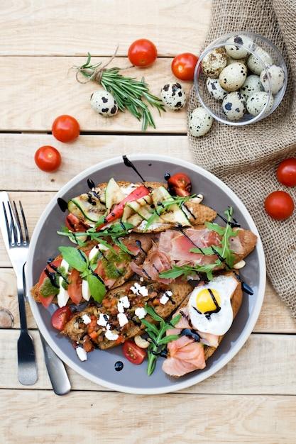 Muchos deliciosos bruschetta con queso, tomate, huevo de codorniz, jamón, salmón, verduras asadas y hierbas Foto Premium