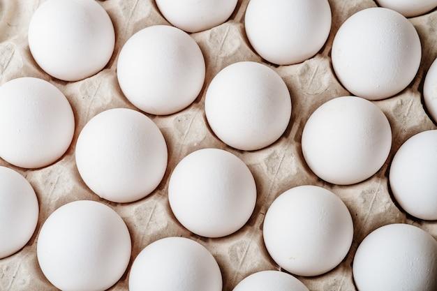 Muchos huevos de gallina blanca comida en caja de la bandeja Foto Premium