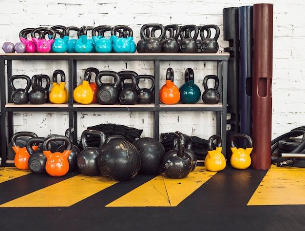 Muchos kettlebells dispuestos en rack en el gimnasio Foto gratis