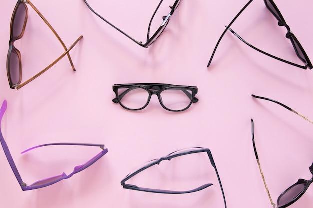 Muchos pares de gafas sobre fondo rosa Foto gratis