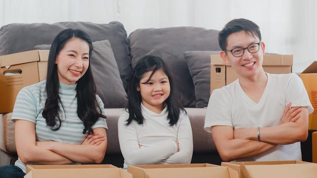 Las mudanzas felices de la reubicación familiar asiática joven se instalan en nuevo hogar. los padres y los niños chinos abren la caja de cartón o el paquete desempacando en la sala el día de la mudanza. vivienda inmobiliaria, préstamo e hipoteca. Foto gratis