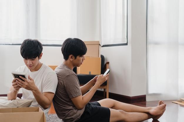 Las mudanzas felices de la reubicación de la pareja gay asiática joven se instalan en un nuevo hogar. asia lover guy lgbtq + caja de cartón abierta o paquete desempacando en la sala de estar el día de la mudanza. vivienda inmobiliaria, préstamo e hipoteca. Foto gratis