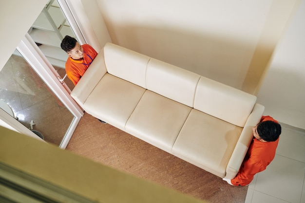 Mudanzas llevando sofá de cuero Foto Premium