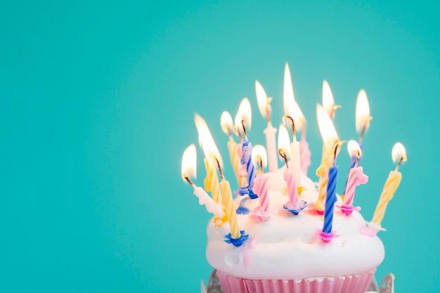 Muffin de cumpleaños delicioso con velas de colores Foto gratis