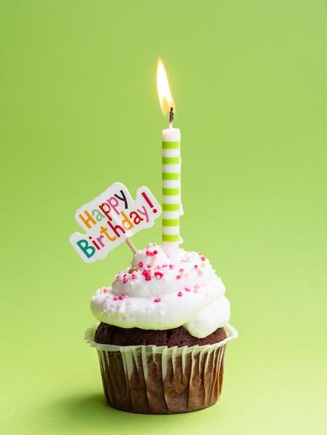 Muffin con vela y cartel de feliz cumpleaños Foto gratis