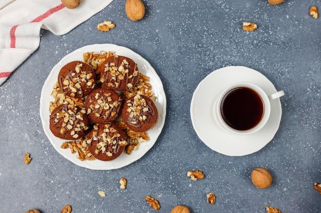 Muffins de chocolate y nueces con una taza de café con nueces sobre una superficie oscura Foto gratis