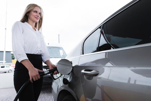 Mujer abasteciendo de combustible en gasolinera Foto gratis