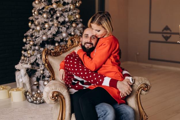 La mujer abraza a su hombre tierno sentado en una silla grande y suave ante un árbol de navidad Foto gratis