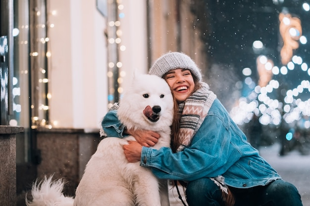 Una mujer abraza a su perro en una calle de noche. Foto gratis