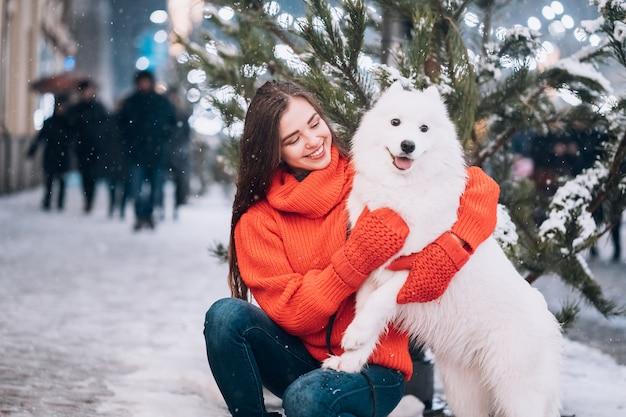 Mujer abraza a su perro en una calle de noche Foto gratis