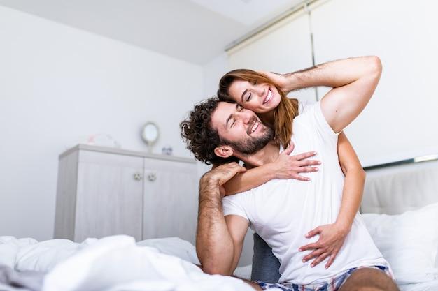Mujer abrazando a su pareja en la cama, feliz pareja en la cama mostrando emociones y amor. hermosa pareja amorosa besándose en la cama. hermosa joven pareja acostada en la cama. Foto Premium