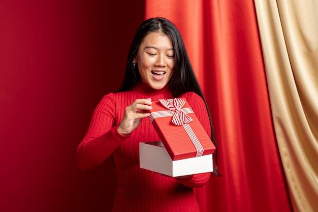 Mujer abriendo la caja de regalo para el año nuevo chino Foto gratis