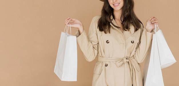Mujer en abrigo beige con muchas bolsas de compras Foto gratis