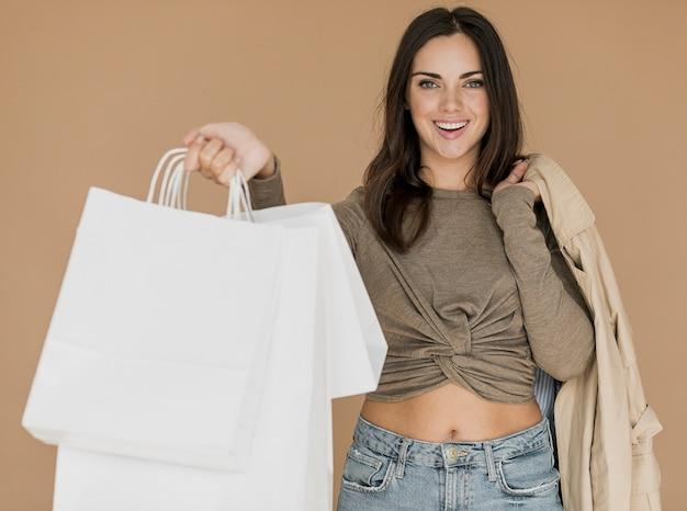 Mujer con abrigo en el hombro y bolsas blancas Foto gratis