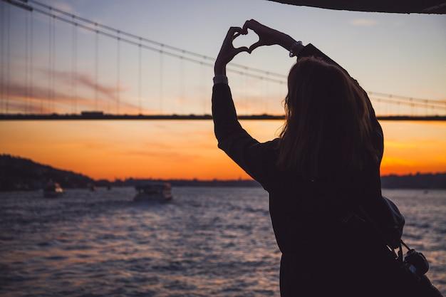 Mujer en abrigo oscuro de pie con las manos en alto haciendo un corazón con el bósforo y la vista del puente en el fondo al atardecer Foto Premium