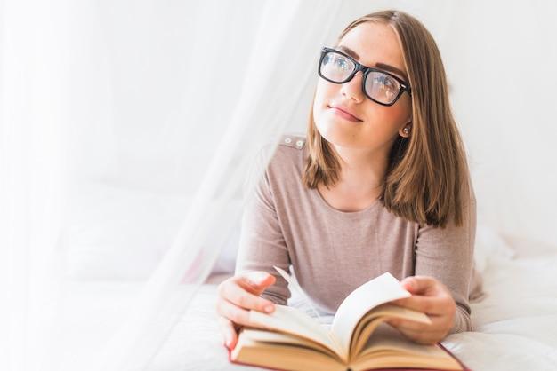 Mujer acostada en la cama con el libro soñando despierto Foto gratis