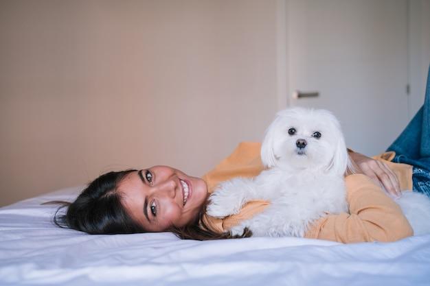Mujer acostada en la cama con su lindo perro maltés Foto Premium