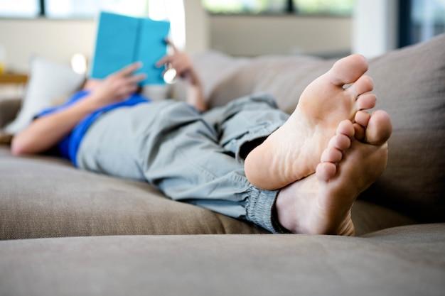 Mujer acostada descalza en el sofá leyendo un libro Foto Premium