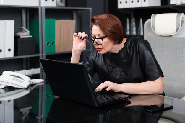 Mujer adulta con gafas de mano y mirando a través de ellas en el monitor en la oficina Foto Premium