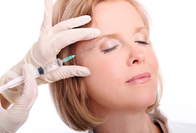 Mujer adulta con inyección facial Foto gratis