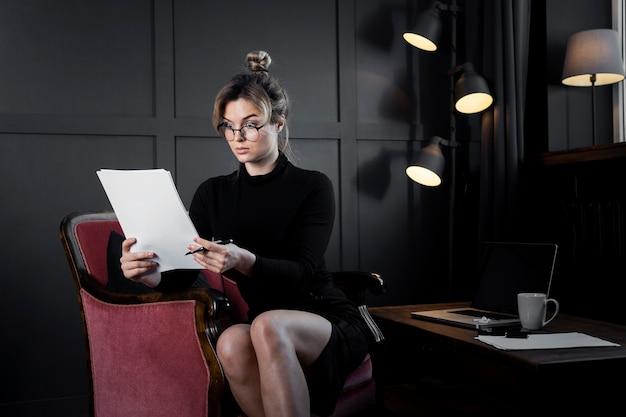 Mujer adulta segura que controla algunos papeles Foto gratis