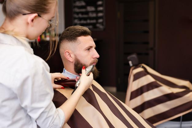 Mujer afeitarse la barba de su cliente con espacio de copia Foto gratis