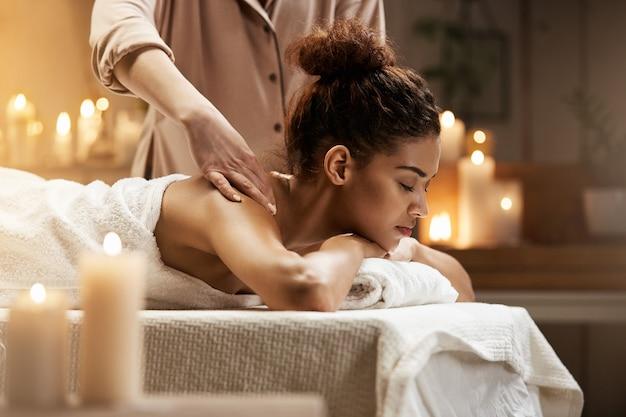 Mujer africana blanda que sonríe disfrutando de masaje con los ojos cerrados en balneario. Foto gratis