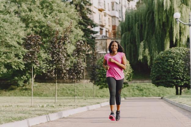 Mujer africana joven sana al aire libre en la mañana. mujer en camiseta rosa. Foto gratis