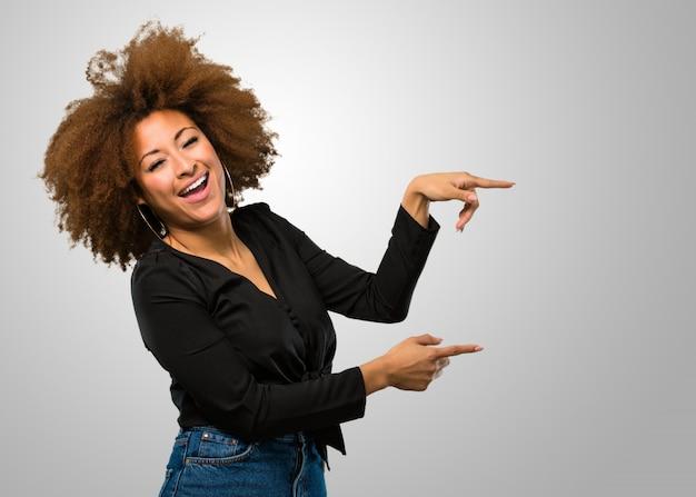Mujer afro apuntando hacia el lado Foto Premium