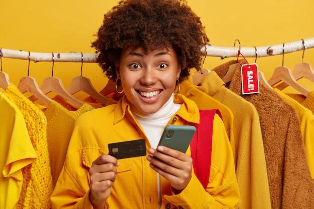 Mujer afro de aspecto agradable verifica la cuenta bancaria, paga en línea a través del teléfono inteligente, tiene tarjeta de crédito Foto gratis