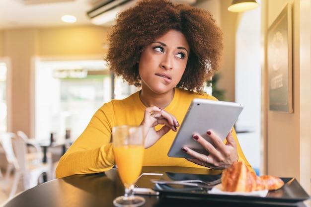 Mujer afro joven que desayuna en el café. ella esta tomando un zumo de naranja Foto Premium